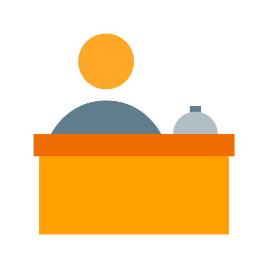 Recepcja icon. The image is a large desk with a little bell on the top right. There is a person behind the desk. The head and upper torso of the person is shown but they have no hair or facial features.