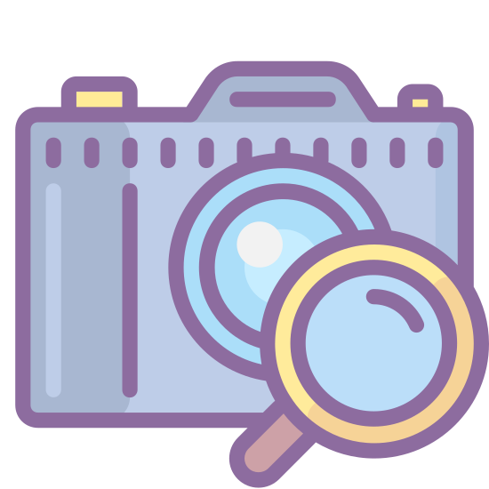 Camera Identification icon. This is an icon of a standard, old style digital camera with a large lens on the front and a small circle in the top left of it. On the bottom right of the camera is a magnifying glass, slightly overlapping it.