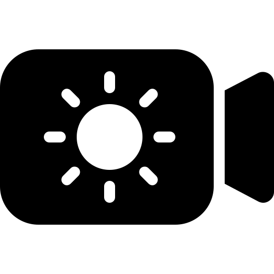 Day Camera Filled icon. This is an image of a camera.  The camera is made of of a slightly rectangular shape, representing the body, and a trapezoidal shape, representing the lens.  Inside the body of the camera is a sun shape composed of a circle with eight small outstretched lines.