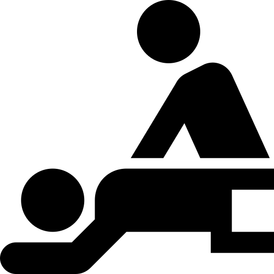 Masaż icon. There are two people in the image. One person is laying down on his stomach with a blanket covering his lower half. The other person is standing above the person laying down and giving him a shoulder massage.