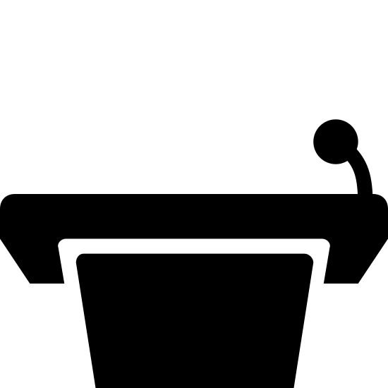 Подиум без спикера icon. This icon represents a podium without a speaker. It is a half square with a top flat rounded rectangle. On the left hand side a small line leads up to a small circle representing a microphone.