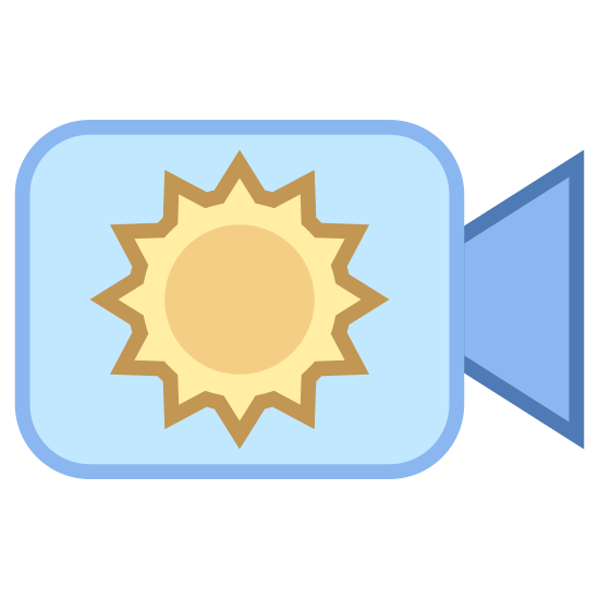 Day Camera icon. This is an image of a camera.  The camera is made of of a slightly rectangular shape, representing the body, and a trapezoidal shape, representing the lens.  Inside the body of the camera is a sun shape composed of a circle with eight small outstretched lines.