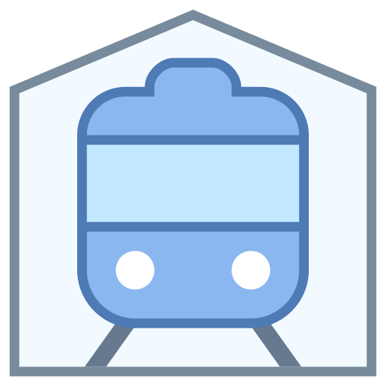 Railway Station icon. The icon is the shape of a pentagon. Inside of the pentagon is the image of the front of a train. The train has to circle headlights at the bottom and window up top.