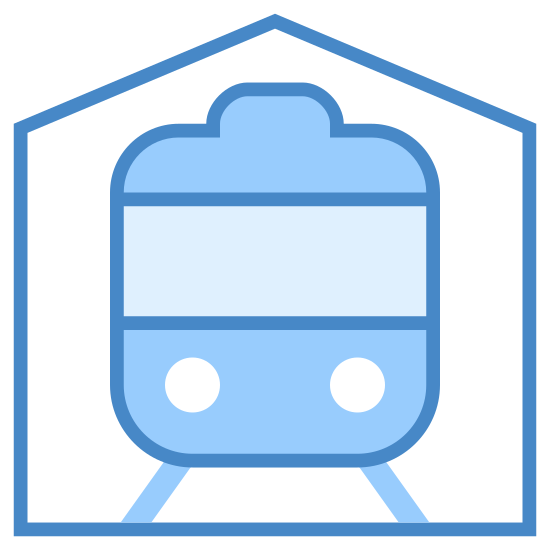 Stacja kolejowa icon. The icon is the shape of a pentagon. Inside of the pentagon is the image of the front of a train. The train has to circle headlights at the bottom and window up top.