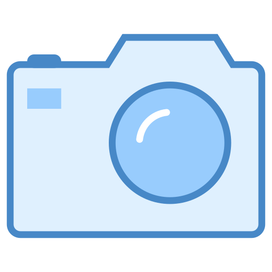 Lustrzanka icon. There is a square with curved edges. On the top of the square there are two areas that protrude. There is also a circle inside the square to depict a camera lens as well as a small dot in the upper right corner.